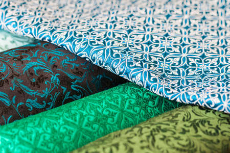 cotton fabric: Rolls of fabric and textiles in a factory shop. Multi different colors and patterns on the market Stock Photo