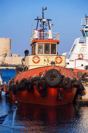 seaport: Tow ship is in the harbor of seaport. Tugboat closeup.