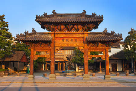 Wuzhen, China - June 24, 2016: Chinese arch, entrance to Park. Wuzhen water village is Shanghai tourist attraction with more than 100000 visitors per year. Wuzhen is part of Tongxiang, located in northern Zhejiang Province, China. Stok Fotoğraf - 128135945
