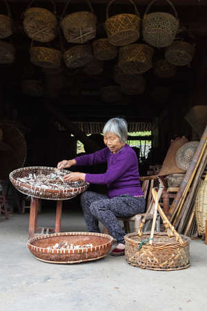Wenzhou, China - April 04, 2016 Chinese woman farmer works hard selecting good and dried bamboo. Chinese vilage. Old chenesse woman