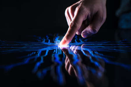 Digitalization Concept: Human Finger Pushes Touch Screen Button and Activates Futuristic Artificial Intelligence. Visualization of Machine Learning, AI, Computer Technology Merge with Humanity Stock Photo