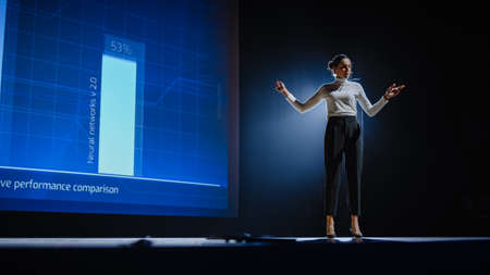 On-Stage Successful Female Speaker Presents Technological Product, Uses Remote Control for Presentation, Showing Infographics, Statistics Animation on Screen. Live Event / Device Release.