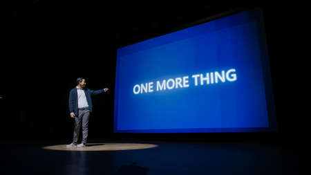 Live Event with Brand New Products Reveal: Keynote Speaker Presents New Device to Audience. Movie Theater Screen Shows Text -One More Thing- and Top Highlights.