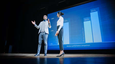 On Stage, Successful Female CEO and Male COO Speakers Present Companys New Product, Show Infographics, Statistics on Big Screen, Talk About Growth. Live Event, Tech Startup, Business Conference