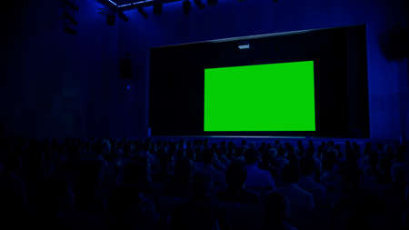In the Modern Movie Theater Captivated Audience Watching New Blockbuster Film on Mock-up Green Screen. People Watching Video Game Tournament Streaming, Live Concert Video, New Product Release Trailer Stock Photo