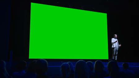Software Startup Founder Does Presentation of New Product to the Audience, Behind Him Movie Theater with Green Screen, Mock-up, Chroma Key. Business Conference Live Event or Device Reveal