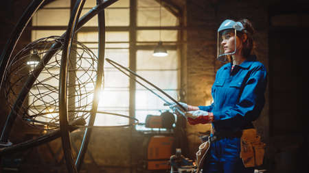 Young Contemporary Female Artist in Blue Jumpsuit and Safety Mask is Fitting a Metal Ring to a Tube Sculpture in a Studio Workshop. Empowering Woman Makes Modern Brutal Abstract Artwork Out Of Steel.