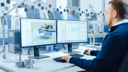 Industrial Engineer Working on a Personal Computer, Two Monitor Screens Show CAD Software with 3D Prototype of Hybrid Electric Engine and Charts. Modern Factory with High-Tech Machinery