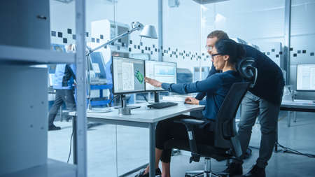 Modern Electronics Factory: Male Supervisor Talks to a Female Electrical Engineer who Works on Computer with CAD Software. Developing PCB, Microchips, Semiconductors and Telecommunications Equipment