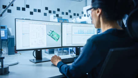 Modern Electronics Factory: Female Electrical Engineer Works on Computer with CAD Software. Developing PCB, Microchips, Semiconductors and Telecommunications Equipment