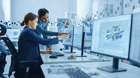 Inside Factory Office: Male Project Supervisor Talks to a Female Industrial Engineer who Works on Computer, Talk. In Workshop: Professional Workers Use High-Tech Industry 4 CNC Machinery, Robot Arm.
