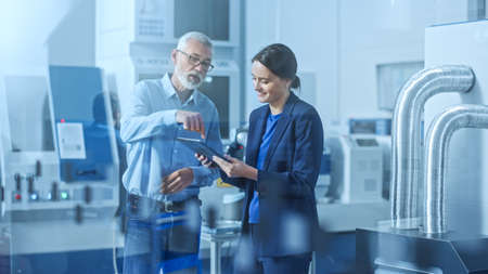 Moderne Fabrik: Ingenieurin, männlicher Projektmanager, der in einer High-Tech-Entwicklungseinrichtung steht, spricht und einen Tablet-Computer verwendet. Zeitgenössische Einrichtung mit CNC-Maschinen, Roboterarm-Fertigungslinie