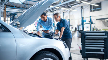 Manager Checks Diagnostics Results on a Tablet Computer and Explains an Engine Breakdown to an Female Mechanic. Car Service Employees Inspect Cars Engine Bay with a LED Lamp. Modern Clean Workshop.