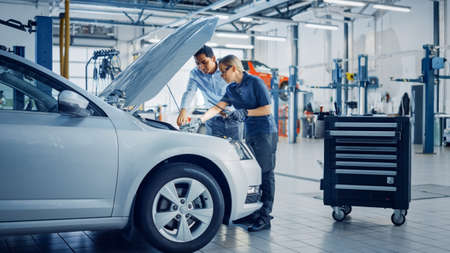 Manager Checks Data on a Tablet and Explains an Engine Breakdown to an Empowering Female Mechanic. Car Service Employees Inspect a Car with Internal Combustion Engine. Modern Clean Workshop.