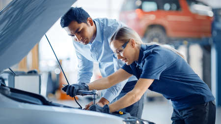 Manager Checks Diagnostics Results on a Tablet Computer and Explains an Engine Breakdown to an Female Mechanic. Car Service Employee Uses a Ratchet to Fix the Engine Component. Modern Clean Workshop.