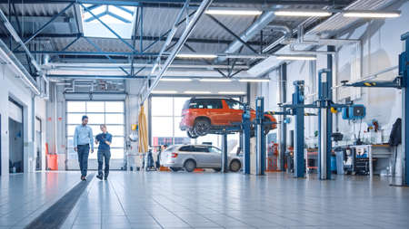 Female Mechanic Checks Diagnostics Results on a Tablet Computer and Explains a Vehicle Breakdown to a Manager. Car Service Employees Talk while Walking in a Garage. Modern Clean Workshop. Stock fotó
