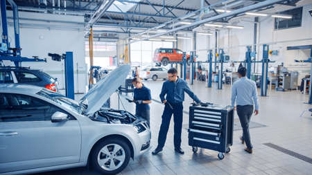 Two Mechanics in a Service are Inspecting a Car After They Got the Diagnostics Results. Female Specialist is Comparing the Data on a Tablet Computer. Repairman is Using a Ratchet to Repair the Faults. Stockfoto