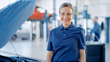 Beautiful Empowering Female Car Mechanic is in a Vehicle Service. She Looks Happy, Smiles and Looks at a Camera. Specialist is Wearing Safety Glasses. Stockfoto