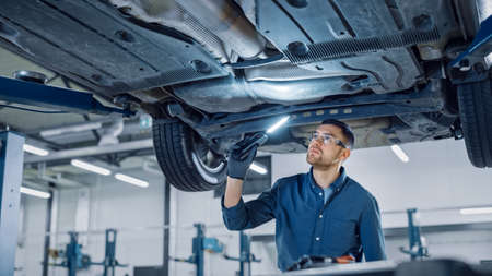 Handsome Professional Car Mechanic is Investigating Rust Under a Vehicle on a Lift in Service. Repairman is Using a LED lamp and Walks Towards. Specialist is Wearing Safety Glasses. Modern Workshop. Banque d'images