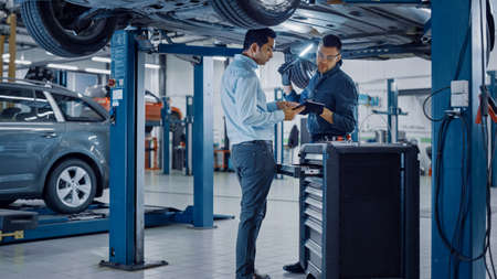 Manager Checks Data on a Tablet Computer and Explains the Breakdown to a Mechanic. Car Service Employees Inspect the Bottom of the Car with a LED Lamp. Modern Clean Workshop. Banque d'images