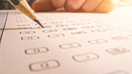 On Exam Test Person Colors Right Answers with a Pencil. Filling up Answer Sheet with Standardized Tests, Marking Correct Answer Bubbles Banco de Imagens