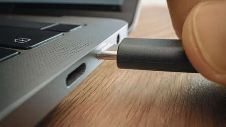 Close-up Macro Shot: Laptop on the Desk, Person Inserts USB-C Cable Adapter into Computer Port.