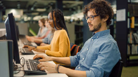 Handsome Bright Boy using Computer for Class Assignment. Diverse Multi-Ethnic Group of Students Learning, Studying for Exams, Work on Computers, Talk in College Study Room