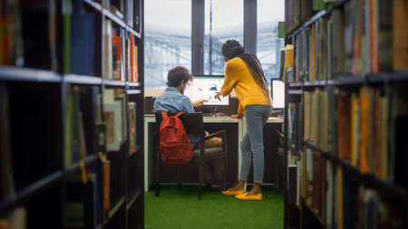University Library: Boy Uses Personal Computer at His Desk, Talks with Girl Classmate who Explains, Helps Him with Class Assignment. Focused Students Study Together. Shot Between Rows of Bookshelves