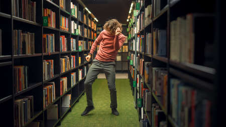 University Library: Handsome Caucasian Student Celebrates Successful Pass of Exams, Dances Between Rows of Bookshelves. Success in College: Admission, Graduations, Finishing Master Thesis