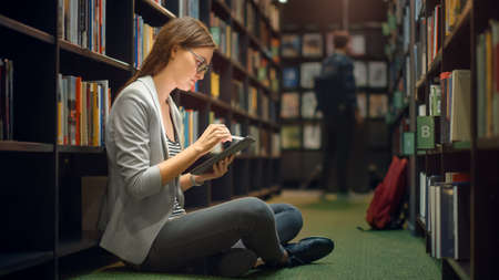 University Library: Beautiful Caucasian Girl Sitting On the Floor, Uses Digital Tablet Computer, Writes Notes, Study for Class Assignment. Diverse Group of Students Learning, Studying for Exams