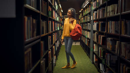 Portrait of Gifted Beautiful Black Girl Stands Between Rows of Bookshelves Searching for the Right Book for Class Assignment. Focused Smart Student Learning, Studying for Exams