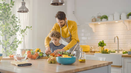 In the Kitchen: Father and Cute Little Son Cooking Together Healthy Dinner. Dad Teaches Little Boy Healthy Habits and how to Cut Vegetables for the Salad. Happy Child and Parent Spend Time Together 写真素材