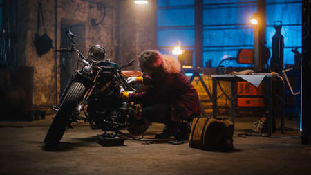 Young Beautiful Female Mechanic is Fixing a Custom Bobber Motorcycle. Talented Girl Wearing a Checkered Shirt. She Uses a Ratchet Spanner. Creative Authentic Workshop Garage.