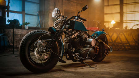 Custom Bobber Motorbike Standing in an Authentic Creative Workshop. Vintage Style Motorcycle Under Warm Lamp Light in a Garage. Stockfoto