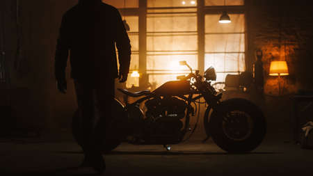 Custom Bobber Motorbike Standing in an Authentic Creative Workshop. Silhouette of a Rider Coming to a Bike. Vintage Style Motorcycle Under Warm Lamp Light in a Garage. Stok Fotoğraf
