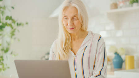 Beautiful Senior Woman Using Laptop Computer in a Sunny Kitchen. She Smiles. Grandmother is Connected with Children via internet and Social Media. Pensioner Working from Home. Imagens