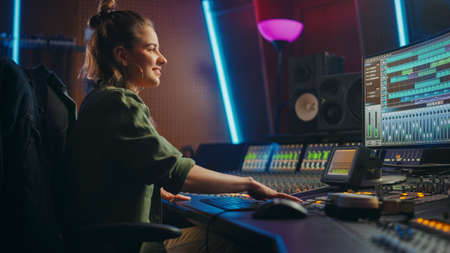 Beautiful, Stylish Female Audio Engineer and Producer Working in Music Recording Studio, Uses Mixing Board and Software to Create Cool Song. Creative Girl Artist Musician Working to Produce New Song