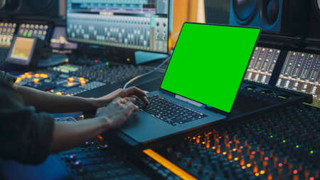 Female Artist, Musician, Producer, Audio Engineer Working in Music Record Studio on a New Album, Use Green Screen Laptop Computer, Control Desk for Mixing and Creating Hit Song Imagens