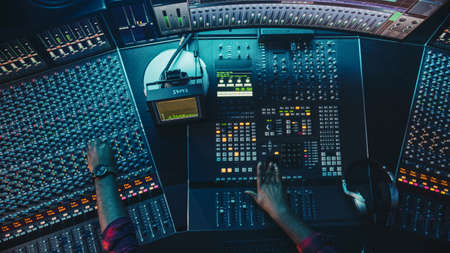 Audio Engineer, Musician, Artist Works in the Music Record Studio, Control Desk Mixer with Equalizer. Hand Moving Fader, Buttons to Broadcast, Record, Play Song. Neon Colors. Top Down View