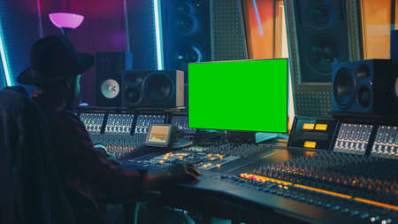 Stylish Audio Engineer Producer Working in Music Record Studio, Uses Green Screen Chroma key Computer Display, Mixer Board Equalizer and Control Desk to Create New Hit Song. Black Artist Musician