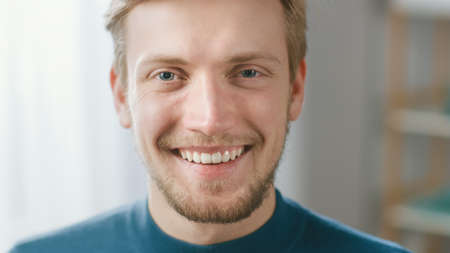 Portrait of Handsome Blonde Young Man Smiling, while Looking at Camera. Happy Attractive Guy with Blue Eyes