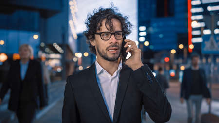 Young Stylish Businessman with Curly Hair is Talking on a Phone While Walking in the City. Hes Wearing Glasses. Office People Walk By. Its Evening with Atmospheric Urban Lights in the Background.
