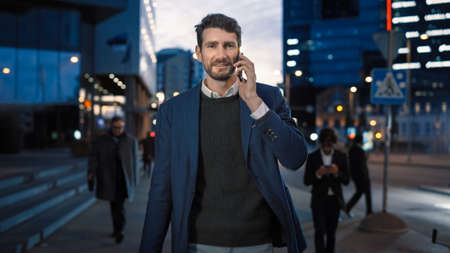 Tall Businessman in a Suit is Talking on a Phone While Walking in the City. Hes Having a Pleasant Conversation. Office People Walk By. Its Evening with Atmospheric Urban Lights in the Background.