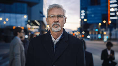 Portrait of a Serious Senior Businessman in a Coat Standing on a Street with Pedestrians. He Has a Beard and Wears Glasses. Its Evening with Atmospheric Urban Lights in the Background.