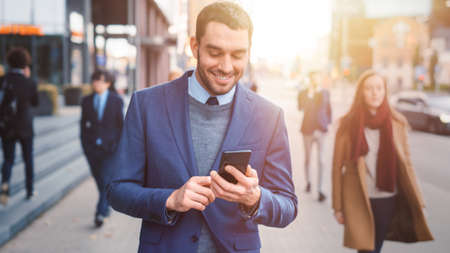Caucasian Businessman in a Suit is Using a Smartphone on a Street in Downtown. Other Office People Walk Past. He Smiles and Looks Successful. Hes Browsing Web on his Device. Shot with Warm Sun Flare.
