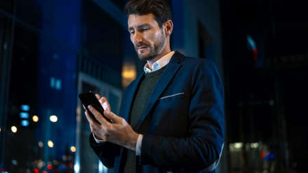 Tall Caucasian Businessman in a Suit is Using a Smartphone on Dark Street in the Evening. Hes Browsing While Looks Confident and Successful. Atmospheric Urban City Lights in the Background.