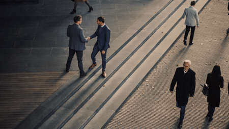 Office Managers and Business People Commute to Work in the Morning or from Office on a Sunny Day on Foot. Pedestrians are Dressed Smartly. Two Businessmen Shake Hands. Shot from Above.