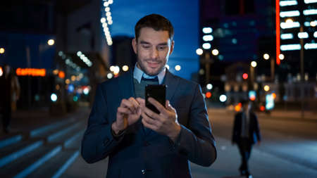 Portrait of Caucasian Businessman in a Suit is Using a Smartphone on Dark Street in the Evening. He Looks Confident and Successful. Atmospheric Urban City Lights in the Background. Reklamní fotografie
