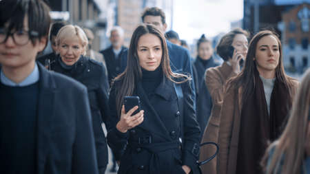 Beautiful Businesswoman in Black Coat is Using a Smartphone on a Street in Downtown. She Walks on a Crowded Pedestrian Street and Looks Successful. Shes Browsing the Web on Her Device.