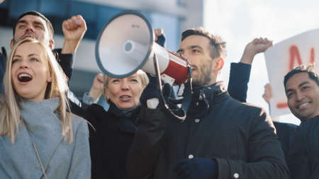 Multicultural Diverse Office Managers and Business People Picketing Outside on a Street. Men and Women Screaming for Justice, Holding a Megaphone, Picket Signs and Posters. Economic Crisis Strike. Reklamní fotografie